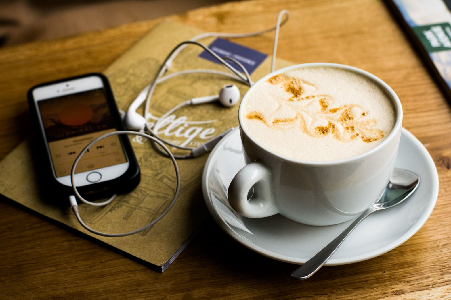 headphones smartphone and latte with a spoon on a cafe table