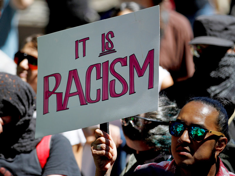 protestor holding a sign that says it is racism