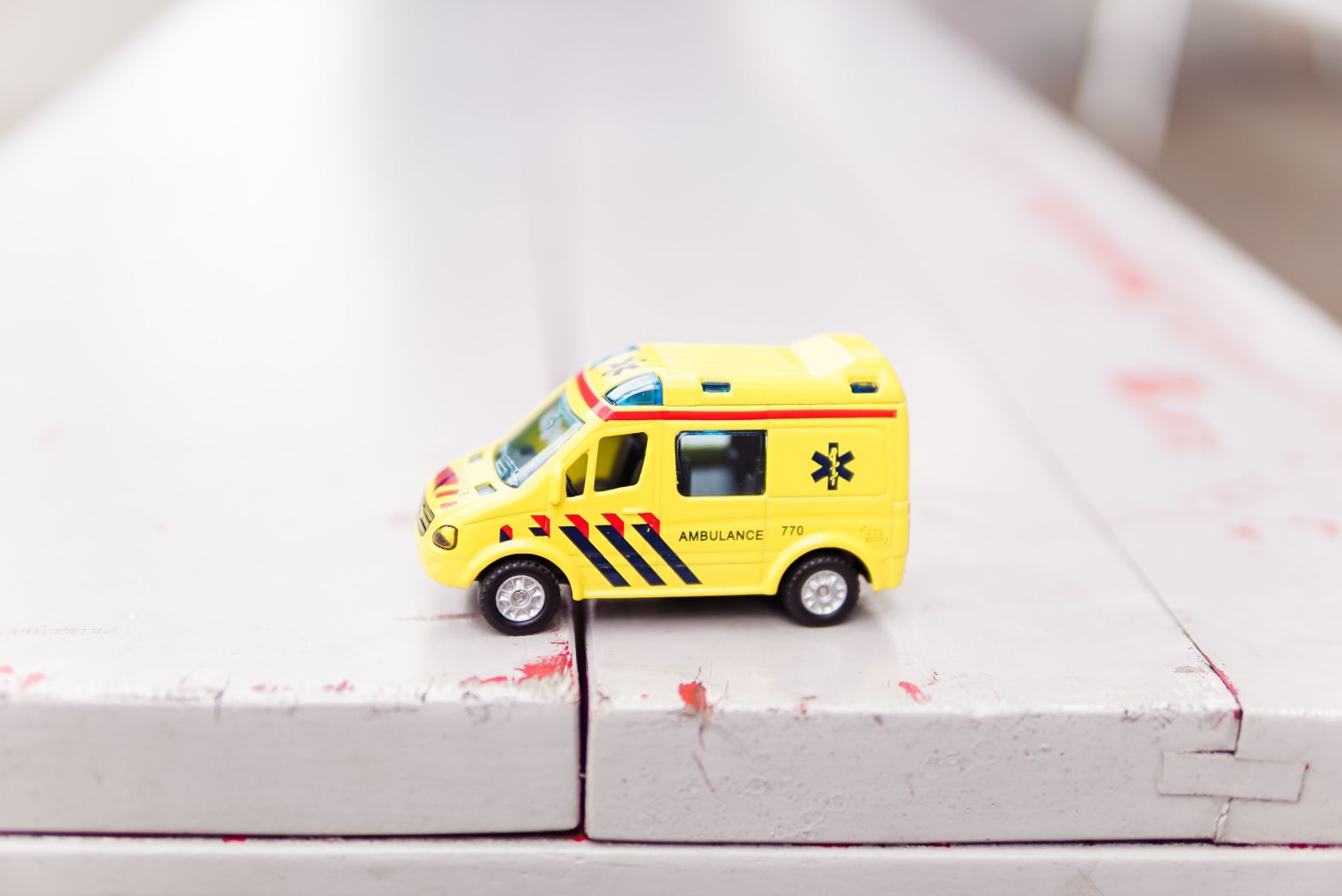yellow toy ambulance truck on white surface