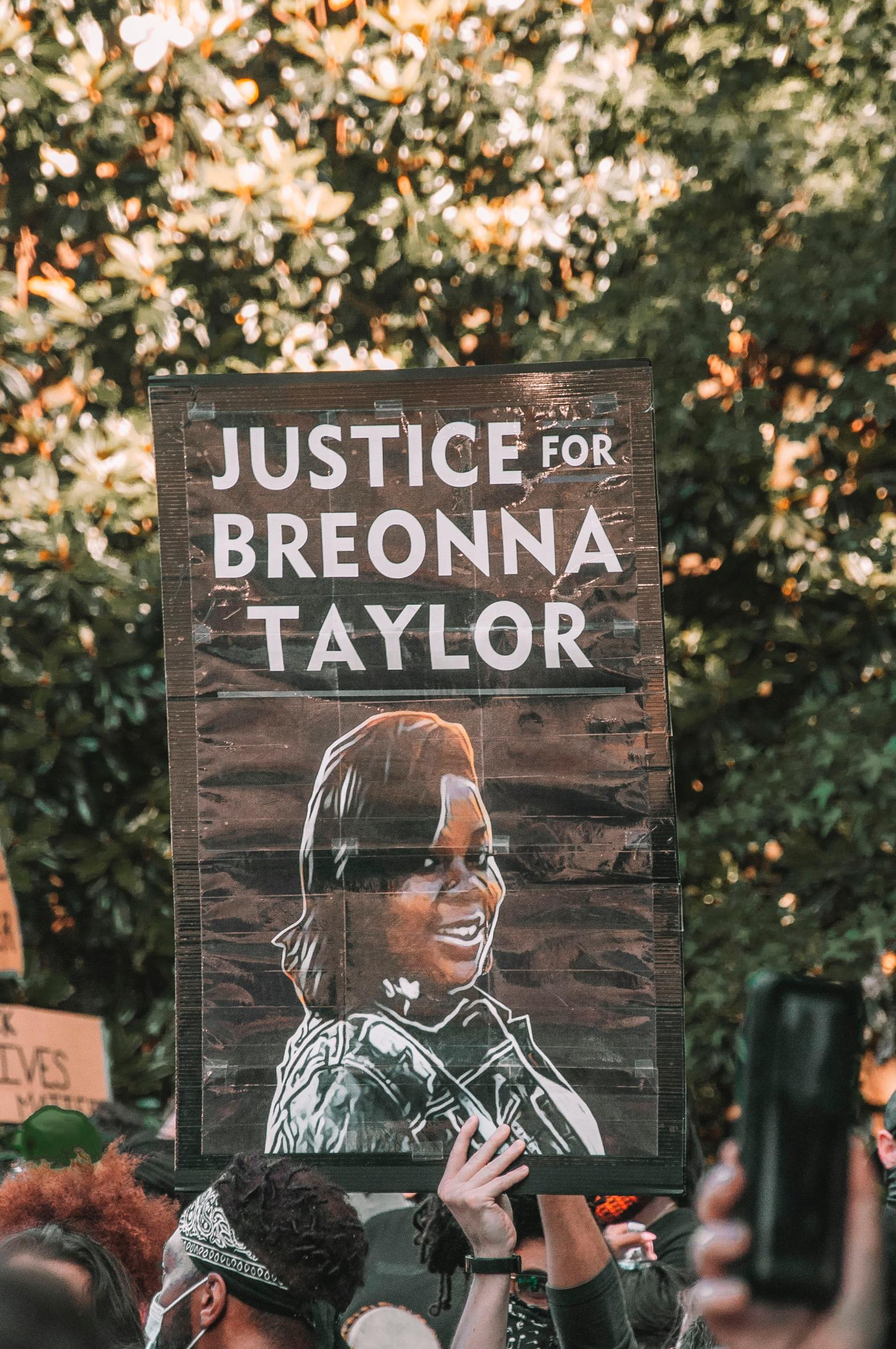poster that reads justice for breonna taylor held by a protestor at an outdoor rally