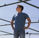 young white man standing on boat in blue shirt