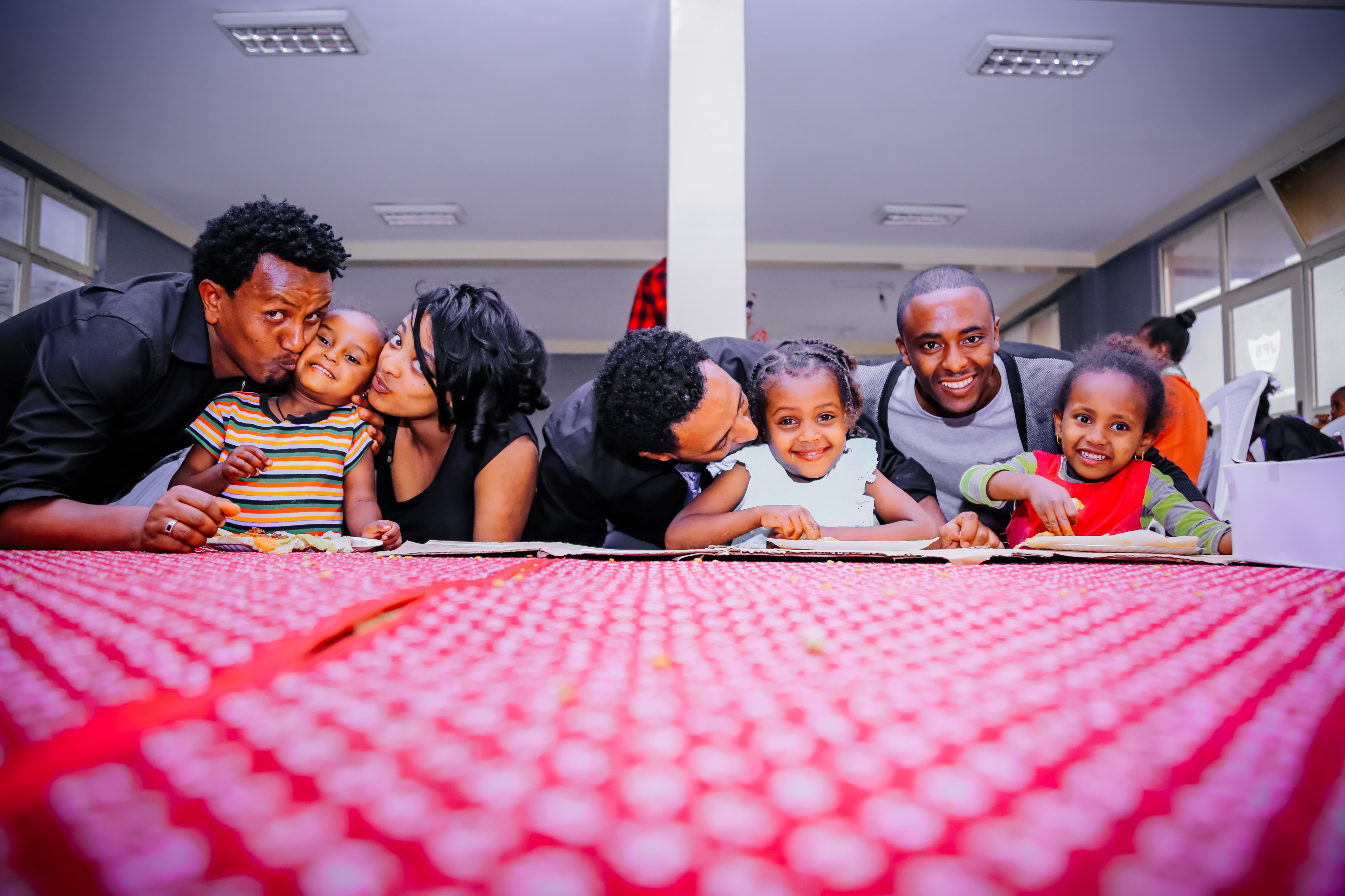 parents and young children of color at a table