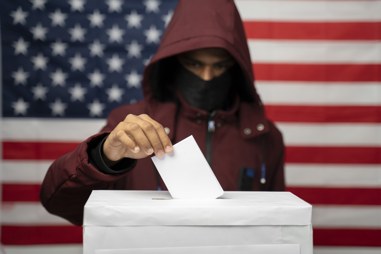 Man in hoodie with face covered casting Vote at polling booth with US falg as background - Concept of unkonwn voting or vote rigging in US elections
