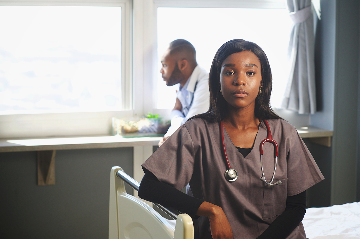 Black Female Doctor sitting on bed with male doctor behind staring out of the window